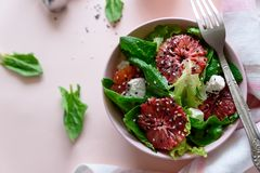 Spring fresh salad with blood orange, lettuce, spinach and sesame seeds on pink background. Top view. Selective focus stock images