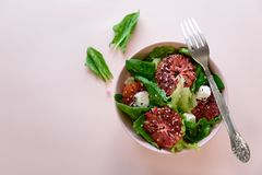 Spring fresh salad with blood orange, lettuce, spinach and sesame seeds on pink background. Top view. Selective focus stock photography