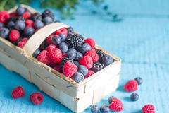 Spring fruits berries in the punnet on blue wooden boards. Closeup royalty free stock images