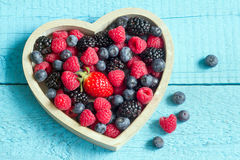 Spring fruits berries in the wooden heart. On blue boards stock photography