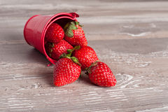 Spring fruits, strawberries in an aluminum bucket. On a vintage wooden table, close up Royalty Free Stock Image
