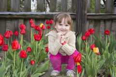 Spring in the garden of a beautiful little girl sitting near tul Stock Image