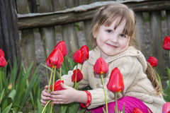 Spring in the garden of a beautiful little girl sitting near tul Royalty Free Stock Photos
