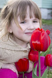 Spring in the garden of a beautiful little girl sitting and smel Royalty Free Stock Images