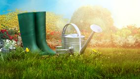Spring garden. Boots and gardening tools in green grass royalty free stock photography