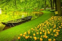 Spring garden with canal and boat. `Keukenhof`, Holland, toned Stock Image