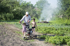 Spring in the garden man plowing land motor-block small son and Stock Photography