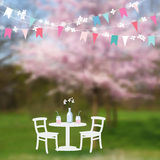 Spring garden party. Table with drinks and paper flags decoration. Modern blurred background with blossoming Japanese Stock Photos