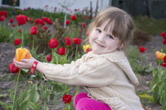 Spring in the garden sitting and smiling little girl holding a t Stock Photo
