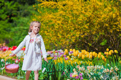 Spring garden, spring flowers, adorable little girl and tulips. Cute kid with a basket in blooming garden on warm day Royalty Free Stock Photography