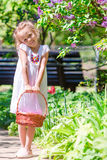 Spring garden, spring flowers, adorable little girl and tulips. Cute kid with a basket in blooming garden on warm day Stock Photo