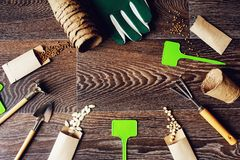 Spring garden work flat lay with vegetable seeds in handmade envelopes. Labels, peat pots and garden tools on wooden table. Seasonal work and preparations stock photos