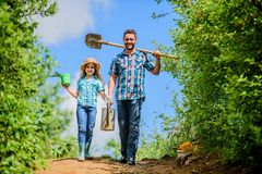 Spring gardening checklist. Father and daughter with shovel and watering can. It is time to plant prepare beds and care royalty free stock image