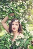 Spring girl face. Pretty young model woman in spring flowers wreath on floral background outdoor stock photo