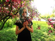 Spring girl with green hair stands under blooming cherry tree, which blooms. Spring girl with green hair standing under the cherry tree, which blooms, flowers royalty free stock photo