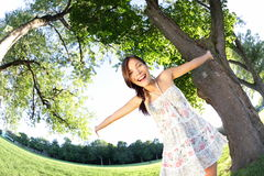 Spring girl happy. Smiling joyful and cheerful in park. Young beautiful mixed race woman dancing outdoors in park in summer dress Stock Image
