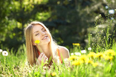 Spring girl lying on the field of dandelions Royalty Free Stock Images