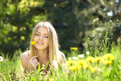Spring girl lying on the field of dandelions Stock Photos