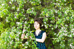 Spring girl portrait. Asian woman smiling happy on sunny summer or spring day outside in flowering tree garden. Pretty Royalty Free Stock Image