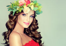 Spring girl.Wreath on the head. Beautiful woman model brunette with long curly hair and floral wreath on the head . Spring girl Stock Photo