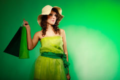 Spring girl young woman with green shopping bags on green Stock Images