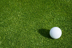 Spring golf. Side view of golf ball on a putting green royalty free stock photo