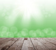 Spring green bokeh with sunlight and wood floor Royalty Free Stock Photo
