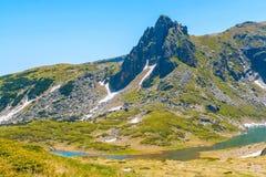 Spring green foliage and snow mountains by Rila Lakes in Bulgaria Royalty Free Stock Photo