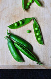 Spring green peas. With pods on wooden chopping board Royalty Free Stock Photography