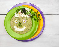 Spring green soup with wild herbs in colorful plates , decorations smile face Royalty Free Stock Photography