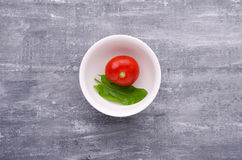 Spring greens for health.  Fresh sorrel  and tomato in plate on Stock Photos