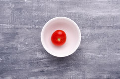 Spring greens for health.  Fresh tomato in plate on grey wooden Stock Photo