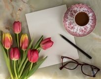 Spring Greeting letter with tulips. Greeting card, bouquet of beautiful flowers, spring tulips, glasses and cup of coffee on a marble background royalty free stock images