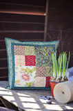 Spring handmade patchwork cushion with narcissus bulbs on wooden table Royalty Free Stock Photography