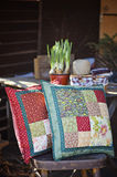 Spring handmade patchwork cushions with narcissus bulbs on background. Handmade patchwork cushions with narcissus bulbs and sewing tools on background in spring Royalty Free Stock Photos