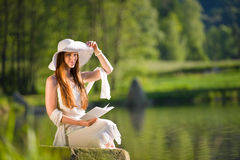 Spring - Happy romantic woman sitting by lake Royalty Free Stock Photos