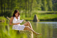 Spring - Happy romantic woman sitting by lake Stock Images