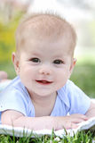 Spring, Happy Smiling Baby in Grass. Spring time, happy smiling baby on tummy in grass Royalty Free Stock Image