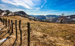 Spring has sprung in rural area. Wooden fence on agricultural field, yellow weathered grass covered with snow. village in the distance at the mountain ridge Stock Photography