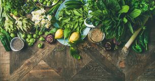 Spring healthy vegan food cooking ingredients, wooden background, wide composition. Spring healthy vegan food cooking ingredients. Flat-lay of vegetables, fruit Stock Photo