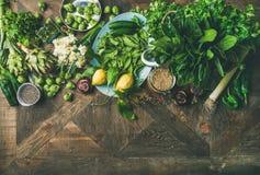 Spring healthy vegan food cooking ingredients over wooden background. Spring healthy vegan food cooking ingredients. Flat-lay of vegetables, fruit, seeds stock photography