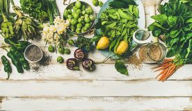 Spring healthy vegan food cooking ingredients, top view, copy space. Spring healthy vegan food cooking ingredients. Flat-lay of vegetables, fruit, seeds, sprouts Stock Images