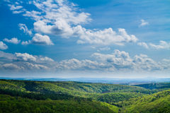 Spring hills with dominant sky. Green hills in the spring with blue sky with clouds stock images
