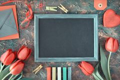 Blackboard framed with red tulips, wooden heart, color chalks an stock photography