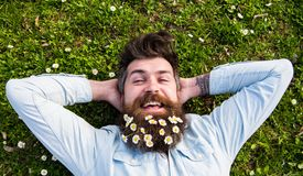 Spring holiday concept. Hipster on happy face lays on grass, top view. Man with beard and mustache enjoys spring, green. Meadow background. Guy looks nicely royalty free stock photos