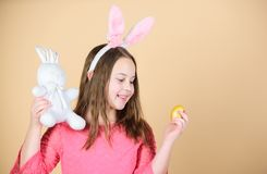 Spring holiday. Little girl holding Easter egg and bunny. Cute child with Easter rabbit bringing egg in spring. Small. Kid with colored egg and hare. Spring stock photo