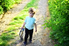 Spring holiday. Sunny weather. Small child with toy in shopping bag. summer. Little boy child in green forest. Happy kid. In blooming nature. Childhood stock images