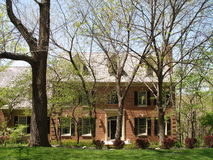 Spring House. A beautiful two story brick house surrounded by trees in early spring Stock Photography