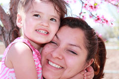 A Spring Hug. A mother and daughter hugging in front of tree blooming in spring Stock Photography