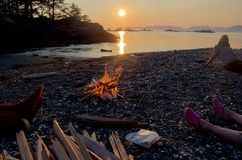 Campfire on beach at sunset with campers relaxing nearby royalty free stock image